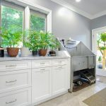 Mudroom With Dogs Wash Sink Station Plus Handheld Shower And Floating Rack For Dogs Shampoo A Credenza Furniture In White With Arrangement Of Decorative Plants  A Grey Mudroom Rug