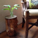 natural brown tree stump side table  a cozy chair with floral patterns pillow a glass pot for water plantation