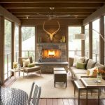 nice open plan sunroom design with glass fence and stone fireplace with cream seating idea upon cream area rug beneath curve floor lamp on wooden flooring idea