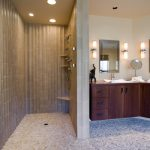no door walk in shower with corner floating bench and floating corner shelves L shape wood bathroom vanity with shiny metal framed mirror and vanity lighting river stones mosaic tiles for floors