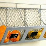 ordinary wire mounted wall fruit basket design wit three slotf filled with orange with black space for note
