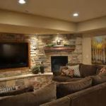 original stone wall design mixed with corrner fireplace and large television in basement theatre finishing