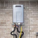 outdoor gray rinnai tankless water heater installation on brick wall plus wires and pipes