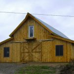 pole barn house with wood siding and metal roofing