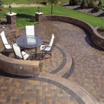 raised brick paver patterns with herringbone pattern and stack bone variation for beautiful patio garden with grass and plants and garden lamp
