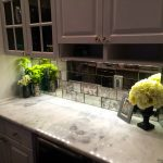 regular mirror tiles for kitchen backsplash white marble kitchen countertop  some beautiful pots with plants a picture frame bottom cabinet and drawers with gold button handles