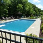 regular rectangle pool designs with pool lounge chairs and green garden plus black metal fences