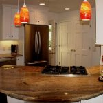 remodel contractor for kitchen with curved kitchen cabinets with wooden countertop and beautiful pendant lighting and refrigerator