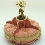 round settee chair with pink seating feature and  gold edges and an ornamental chandelier at the center
