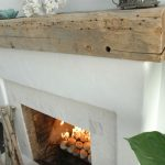 rustic boxy driftwood mantle design upon white fireplace aside big greenery befoe comfortable modern seating