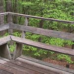 rustic horizontal wooden railing idea with rustic wooden floor hovering on the ground beneath lush vegetation