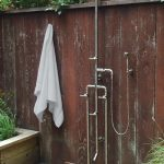 rustic outdoor shower space with free standing shower fixture