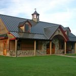 rustic pole barn construction as home living with natural stones exterior decoration and wood pillars  two attics buildings wood siding and metal roofing