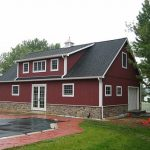 semi  modern pole barn house with red painted metal siding and natural stones base  white wood window and door trims