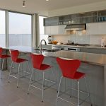 series 7 barstools in red with stainless steel legs  metal kitchen island with sink and faucet metal kitchen counter with gas stove and other kitchen appliances top kitchen cabinets  top glass door shelves