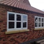 simple cottage style windows in white made by solid wood frame plus clear glazing together with brick wall