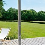 simple free standing stainless steel outdoor shower head fixture in wood planks floors an outdoor chair