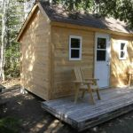 simple rustic cabin with wood planks wall and floor systems  a pair of wood chairs a pair of small windows and a front door