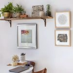 single floating plant shelf for indoor with only two pots of vivid plants some decorative paintings on wall