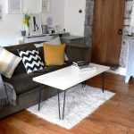 Small Hairpin Table With White Wood Surface And Blacken Finish Legs Small White Fury Carpet Light Black Fury Coat Sofa With Colorful Pillows A Small Entry Door With Classic Design Hardwood Floor Idea