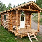 small rustic cabin made from logs some hanging plant decorations a small white bench