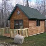 small rustic cabin with wood planks wall and wood fence system in the woods
