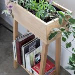 small shelf for indoor plant above an arragement of books