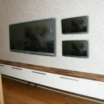 sophisticated white long media console with natural wooden countertop beneath triple tv screen upon wooden floor with decorative plant