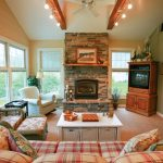 spacious sunroom design with giant fireplace with stone mantel before table cloth patterned sofa and white coffee table with corner storage