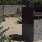 Splendid Black Modern Mail Box Design With Brown Wooden Accent Above Rustic Gray Concrete Beam In The Middle Of Deserted Area