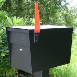 Stunning Modern Mail Box Design In Boxy Shape With Orange Lock In The Middle Of Greenery With Black Metal Beam