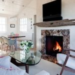 stunning rustic driftwood mantle design upon stone fireplace beneath television before white seating and glass coffee table