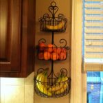 sweet tall three levels wall mounted fruit baskets design with banana and orange stacked on yellow wall aside wooden cabinet and draped window