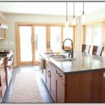 three pendant lamps for kitchen a kitchen island with storage system and bastools and also sink plus faucet