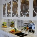 traditional antique mirror installation for kitchen backsplash  double sinks with double faucets a wood cut boarwith some vegetables on it white marble kitchen counter white bottom cabinets