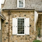 traditional cottage building with cottage window with opened wood window panels natural stones wall system