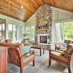 traditional sunroom design with wooden ceiling and white framed glass door and window and concrete floor and wooden seating and stone mantel fireplace
