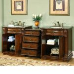 traditional vanity in darker stained wood with double small and round sinks and gold faucets a pair of tree painting as wall decorations luxurious rug