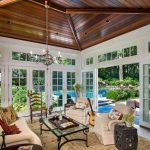 tropical sunroom design with stunning wooden ceiling and white framed glass door idea with white seating design and black metal coffee table with guitar accent and chandelier with cream area rug