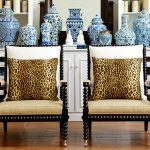 twin spool chairs with ornamental legs and back features plus animal skin prints an arrangement of antique and expensive vases