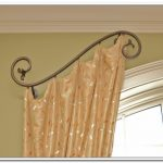 unique and artistic hal curtain rod design with curve style and peach patterned curtain on evening hue wall