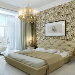 unique and luxurious chandelier above maestic bedding set with cream quilt and decorative tufted headboard beneath big photo on floral patterned wall decoration and candle nighstand with white chair