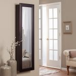 vertical floor to ceiling mirror with black frame two decorative vases a settee furniture in white a picture frame