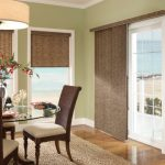 Vertical Grey Window Covering For Sliding Glass Door In Neutral Grey Room With Dining Table And Tall Backrested Chairs Beneath Round Chandelier