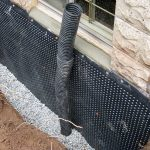 waterproof basement for home exterior with membrane waterproofing and black plumbs in natural wall