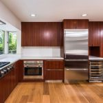 wax-finish wood cabinets for kitchen that have metal handles large gas stove units some modern kitchen appliances softwood floors