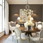 white cowhide leather chairs in dining room beneath luxurious chandelier above grey modern area rug with large glass window with white curtain and wall pallete on grey beadboard