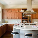 white curved kitchen island with wooden cabinets and countertop plus sinks and stools and pendant lamps and wooden floor