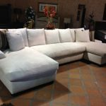 white double chaise sectional with flashing black white cushion and beige small tiles flooring idea with room flower decoration and blaclk wooden cabinetry
