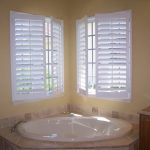 white shutter for swing windows' panels  a built in white corner tub with stainless steel faucet a bathroom vanity with storage and marble surface